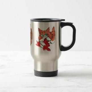 El gatito está jugando con tres hojas de arce roja taza