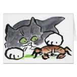 El gatito ha encontrado un cangrejo en la playa felicitaciones