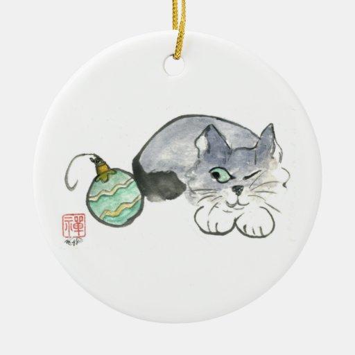 El gatito observa un ornamento del verde y del adorno redondo de cerámica