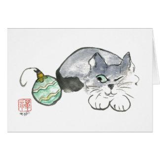 El gatito observa un ornamento del verde y del oro tarjeta de felicitación