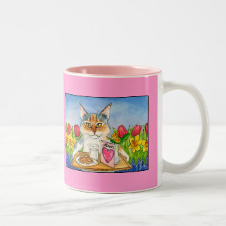 El gato ama la taza rosada del día de madre