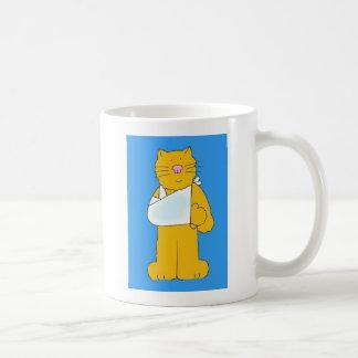 El gato con el brazo en una honda consigue bien taza de café