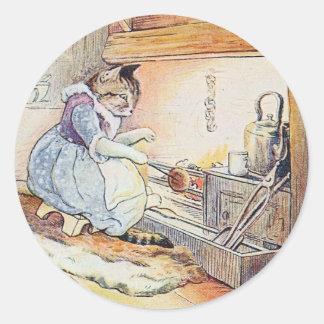 El gato del gatito se sienta por el fuego pegatina redonda