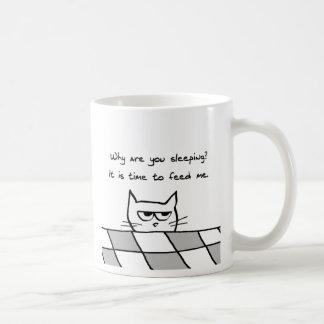 El gato enojado le quiere fuera de cama taza