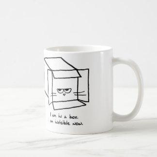 El gato enojado oculta en una caja taza básica blanca