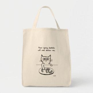 El gato enojado tiene gusto de conseguir en el bolsa tela para la compra