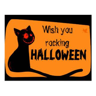 El gato negro con rojo observa la tarjeta de postales