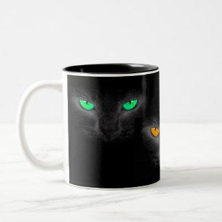 El gato negro hace frente a la taza de café