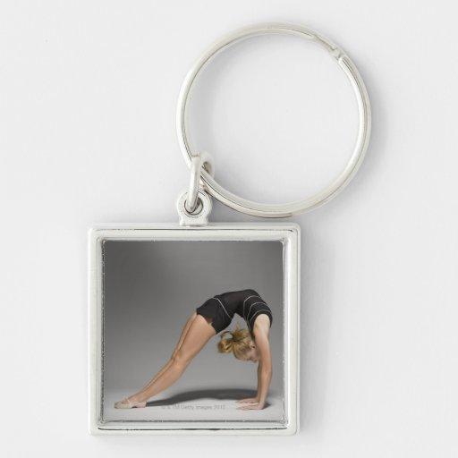 El gimnasta de sexo femenino que estiraba, estudio llavero cuadrado plateado
