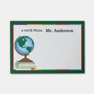 El globo del mundo en la pila de libros notas post-it®