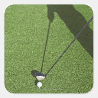 El golfista con el conductor se prepara para el pegatina cuadrada
