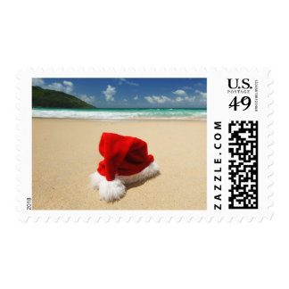 El gorra de Santa en una playa tropical Sello