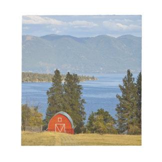 El granero rojo se sienta a lo largo del lago de c libreta para notas