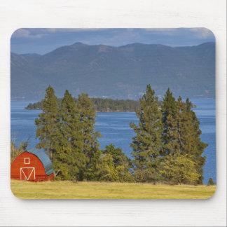 El granero rojo se sienta a lo largo del lago de c tapete de ratones