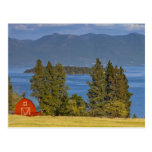 El granero rojo se sienta a lo largo del lago de postal