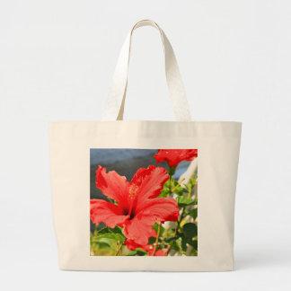 El hibisco rojo florece la bolsa de asas