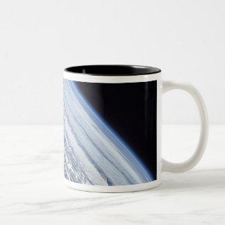 El horizonte de la tierra contra la negrura del taza de café de dos colores