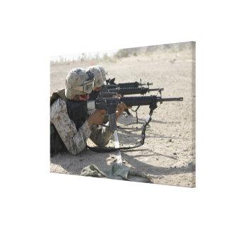 El infante de marina enciende sus rifles de impresiones en lona