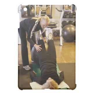 El instructor ayuda al cliente mayor con estiramie