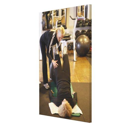 El instructor ayuda al cliente mayor con estiramie impresión en lona