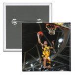 El jugador de básquet que salta en aire pin cuadrado