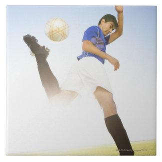 El jugador de fútbol salta el retroceso con el pie azulejo cuadrado grande