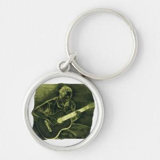 el jugador de la guitarra acústica sienta el amari llavero redondo plateado