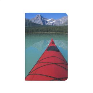 El Kayaking en el lago waterfowl debajo del pico Cuaderno