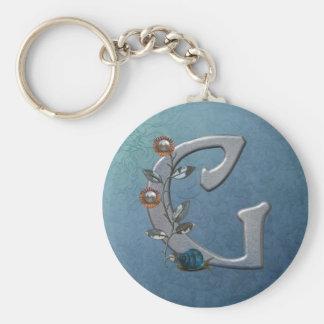 El metal florece el monograma G Llavero