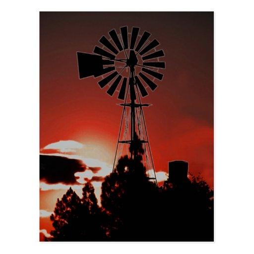 El molino de viento viejo en la puesta del sol postal