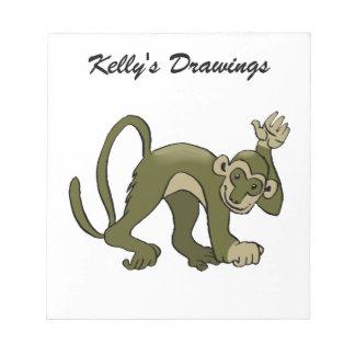 El mono agita en usted libreta para notas