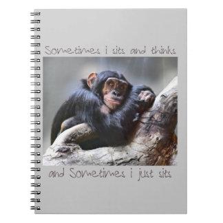 El mono se sienta libros de apuntes