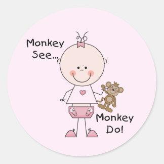 El mono ve el mono hacer las camisetas y los pegatina redonda