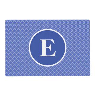 El monograma blanco azul circunda el modelo salvamanteles