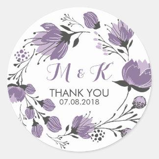 El monograma floral púrpura de la guirnalda le pegatina redonda