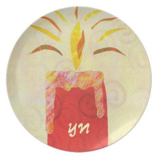 El monograma que destella de la luz de una vela plato