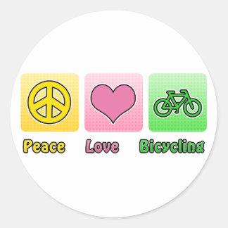 El montar en bicicleta del amor de la paz pegatina redonda