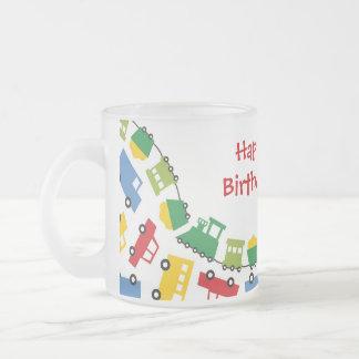 El muchacho del cumpleaños juega los camiones taza de café esmerilada
