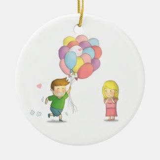 El muchacho lindo comparte su amor al chica con adorno navideño redondo de cerámica
