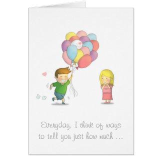 El muchacho lindo comparte su amor al chica con tarjeta de felicitación