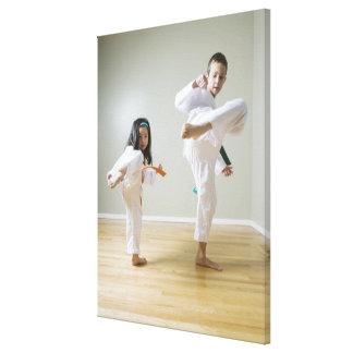 El muchacho y el chica (4-9) el Taekwondo practica Lona Estirada Galerías
