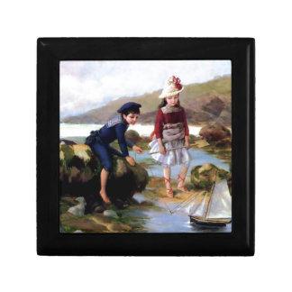 El muchacho y el chica que juegan con la vela del  caja de regalo