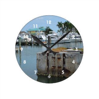 el muelle aherrumbrado pie perfora el puerto reloj redondo mediano