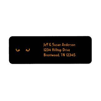 El naranja del gato negro observa etiquetas de etiqueta de remite
