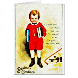 El navidad que saluda con un muchacho sostiene los tarjeta de felicitación