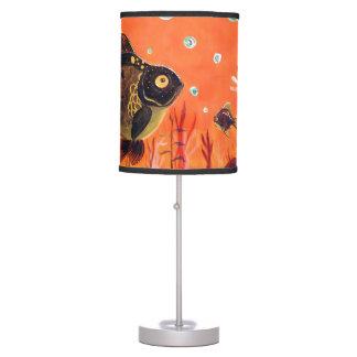 El negro amarra la lámpara de mesa del Goldfish