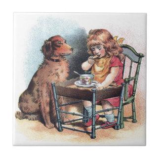 El niño de observación del perro come azulejo cuadrado pequeño