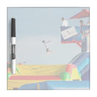 el niño que salta de paseo en el carnaval tablero blanco