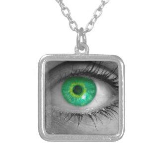 El ojo con el iris verde mira macro del concepto colgante cuadrado