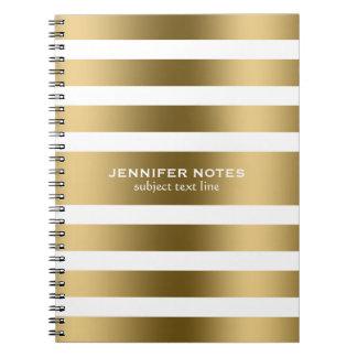 El oro elegante raya el fondo blanco cuaderno